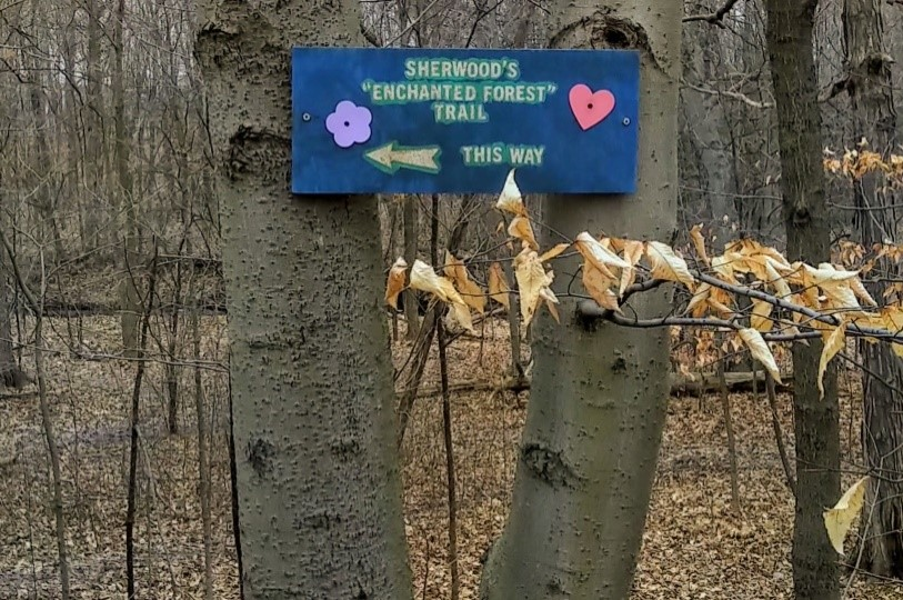"""Sign on tree saying """"Sherwood's Enchanted Forest Trail this way"""""""